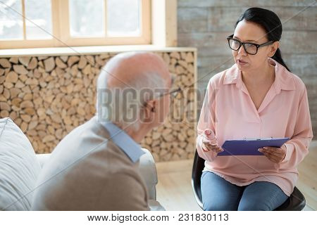Health Monitoring. Appealing Skillful Caregiver Carrying Clipboard While Wearing Glasses And Interro