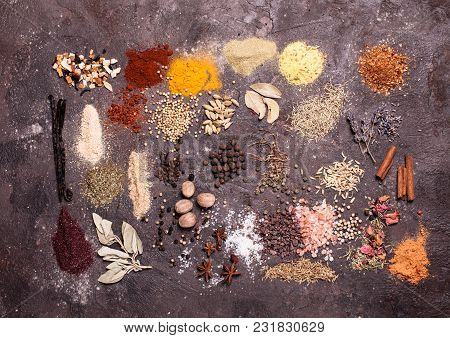 Various Spices Heaps On The Brown Slate Background, Top View