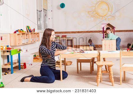 Beautiful Teacher In The Kindergarten Loving Her Job