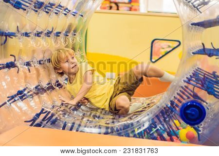 Cute Little Boy, Playing In Zorb A Rolling Plastic Cylinder Ring With A Hole In The Middle, Intdoor.