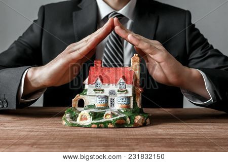 Real Estate Agent Protect A House With His Own Hands. Real Estate Business.