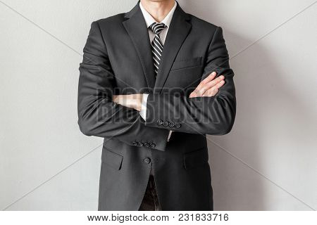 Businessman With White Shirt In Suit And Tie Standing With Crossed Arms On Grey Background