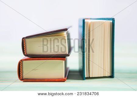 Pile Of Miniature Books On Wooden Background. With Copy Space For Your Text
