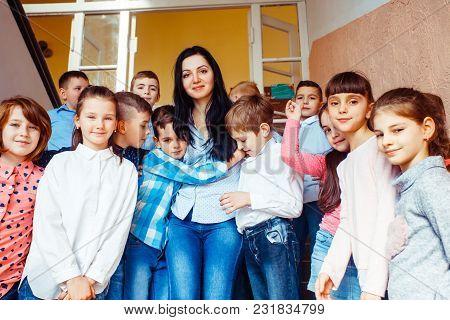 Teacher With Pupils In A School Hallway