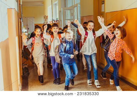 Happy Pupils Running Out Of The Classroom On Summer Vacation