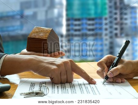 Home Broker Hold A Wooden House Model In Hand.pointing Customer Signs Contract,background Is Blurred