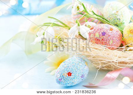Easter colorful eggs background. Beautiful colorful eggs with decorations over blue wooden background, border design in pastel colors. Spring Flowers, holiday ribbon and painter eggs in the nest