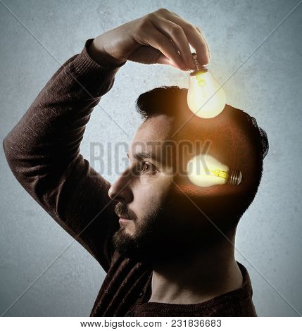 The Man Is Putting A Light Bulb In His Head. The Concept Of New Idea.
