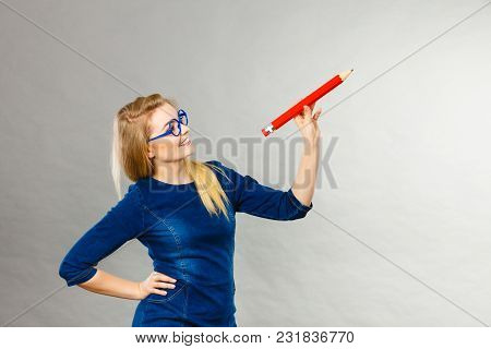 Positive Smiling Woman Blonde Student Girl Or Female Teacher Holding Big Red Pencil Drawing. Studio