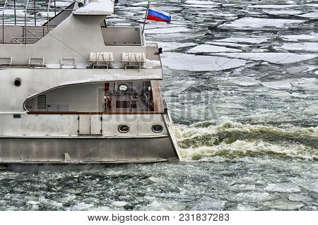 Stern Of Russian Ship With Russian Flag Sailing Along The Moscow-river Covered With A Broken Ice In