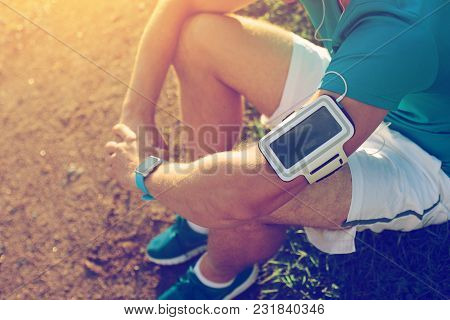 Tired Athlete Sitting And Resting In The Park After Exercises, Outdoors