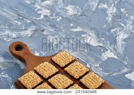 Top View Close-up Picture Of Tasty Square Chocolate Cookies On The Brown Wooden Cutting Board Over A