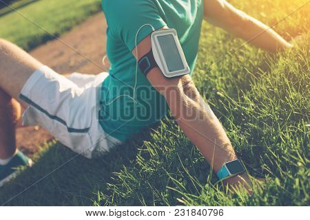 Athlete Sitting And Resting In The Park After Exercises, Outdoors