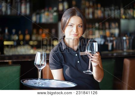 A Barmaid Girl Carries A Wine Glasses On A Tray To The Client Of The Hotel Bar. The Concept Of Servi