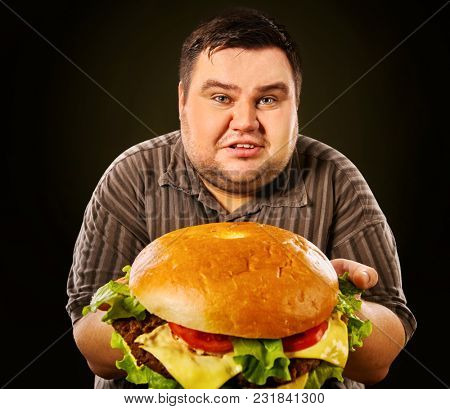 Man eating fast food hamberger. Fat person made great huge hamburger and admires him, intending to eat it. Junk meal leads to obesity. Health problems due to malnutrition.