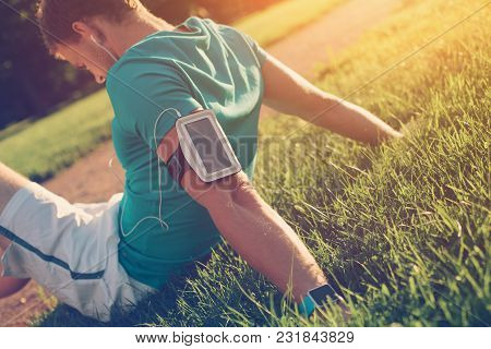 Athlete With Smart Watch And Wristband Resting On The Lawn In The Park After Exercises, Outdoors