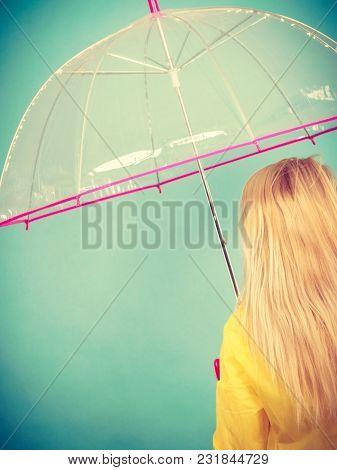 Rainy Autumn Day Accessories Ideas Concept. Blonde Woman Wearing Raincoat Holding Clear Transparent