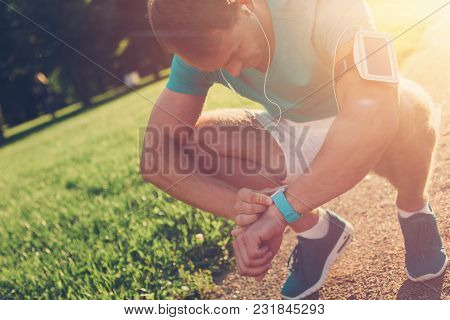 Tired Athlete Resting After Workout In The Park, Lens Flares