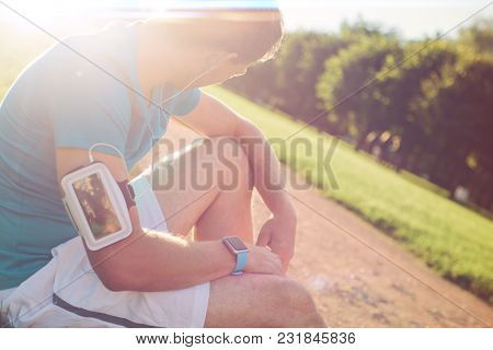Young Tired Athlete With Armband Resting In The Park, Sun Glare And Lens Flares