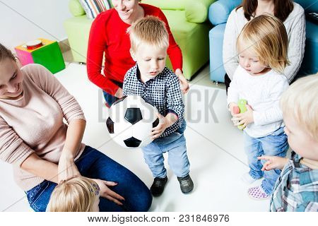 The Group Of Little Kids Quarrel Over A Ball. Children In Hysterics, Because One Boy Intercepted The