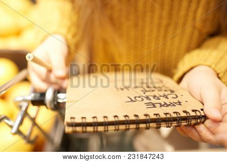 Close Up Of Unrecognizable Little Girl Holding Shopping List While Buying Groceries In Supermarket