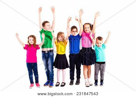 The Happy Kids Are Standing Together  In Colorful Clothes Isolated On White Background