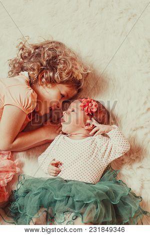 Little Girl With Her Newborn Sister On A Fur Carpet