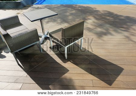 Chairs And Table Side Near The Pool Ideal For Travel And Vacation Concept.bright Sunny Day And Shado