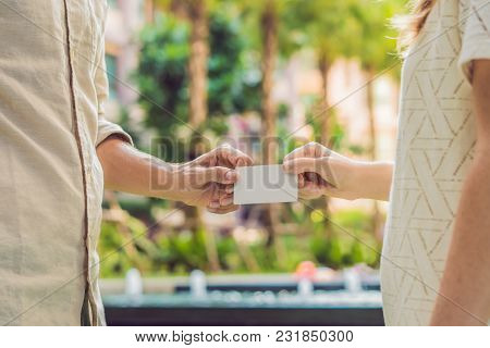 A Woman Gives To A Man Security Key Card Or Business Card.