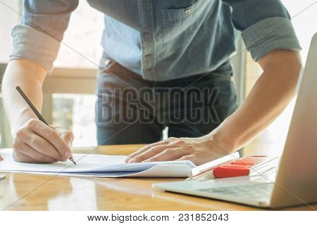 Architects Are Writing With Home Plan And Laptop On The Desk,for Home Design Concepts.