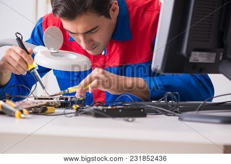 Professional repairman repairing computer in workshop