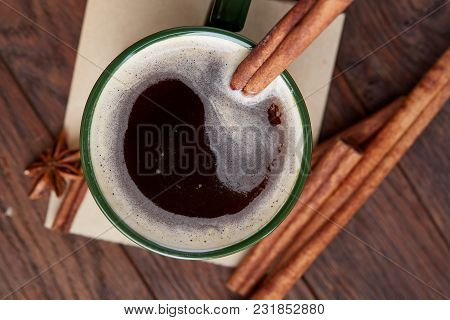 Green Porcelain Cup Of Creamy Coffee With Cinnamon Sticks And Star Anise On A Vintage Wooden Table,