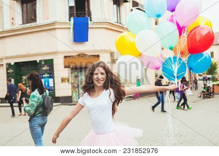 Teenage Birthday. Pretty Girl With Big Colorful Balloons In The Street Of An Old Town