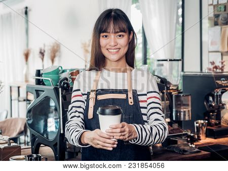 Asian Woman Barista Wear Jean Apron Holding Hot Take Away Coffee Cup Served To Customer With Smiling