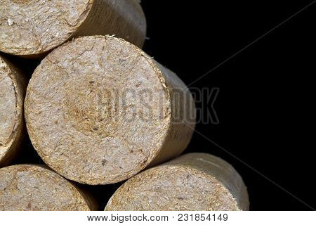 Wood sawdust briquettes straightened, black background. Alternative fuel, bio fuel. poster
