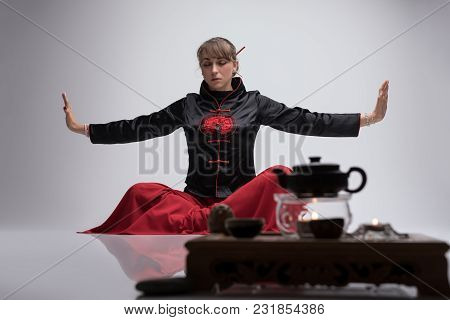Woman Wearing Traditional Chinese Clothes Practicing Wushu By Table Laid For Chinese Tea Ceremony Sh