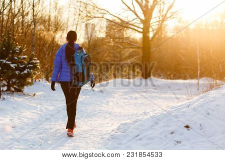 Image From Back Of Walking Sports Woman With Backpack In Winter Forest During Day