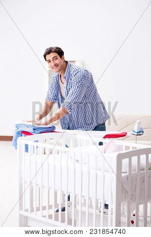Young dad looking after newborn baby