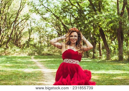 Beautiful Princess With Crown In Cloudy Red Dress Standing On The Path In Fairy Tale Forest.