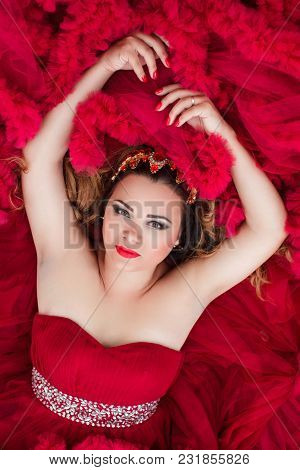 Beautiful Fashion Woman In Red Cloud Dress Laying On The Sofa. Close Up Face Portrait