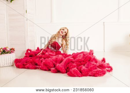 Long-hair Blonde Woman In Red Cloud Dress Posing In The White Hall