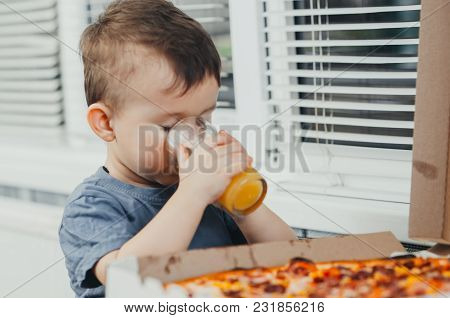 The Child In The Kitchen Drinks Orange Juice And There Is A Large Pizza