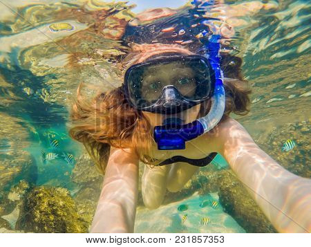 Woman Snorkeling In Tropical Waters In Front Of Exotic Island.