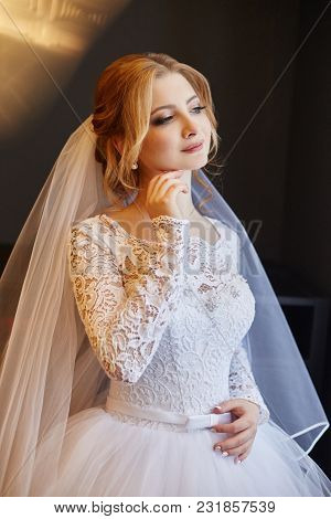 Beautiful Bride In White Wedding Dress On Wedding Day. A Woman Is Waiting For Her Fiancé Before The