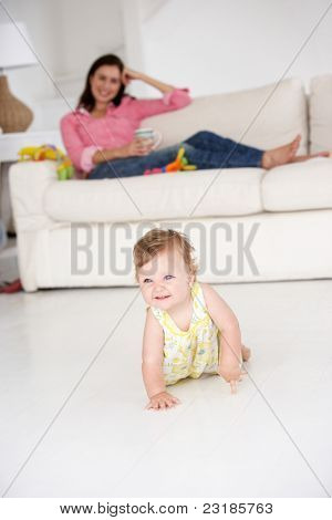 Mother watching baby crawl