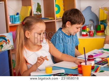 Small students girl and boy painting in art school class. Child drawing by paints on table. Unusual ways of drawing. Craft drawing education develops creative abilities of children.