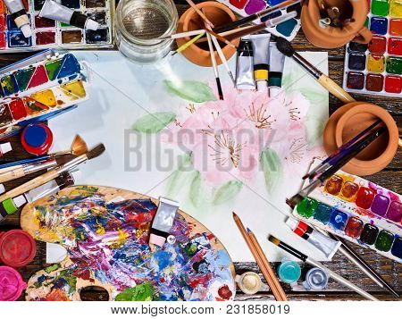 Authentic paint brushes still life in art class school. Group of brush in clay jar. Bouquet of tulip flowers as symbol of spring discounts. Flowers with watercolor. Spring discounts on drawing course.