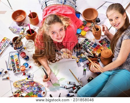 Authentic artist children girl paints with set palette watercolor paints palette and brush in morning sunlight. Painting in studio on floor. Home interior handmade crafts. Materials for artist.