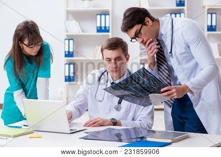 Three doctors discussing scan results of x-ray image