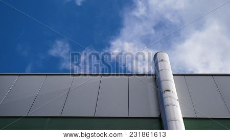 Low Angle View Of Industrial Factory Chimney With Grey Smoke Over Bright Sunny Sky In England.
